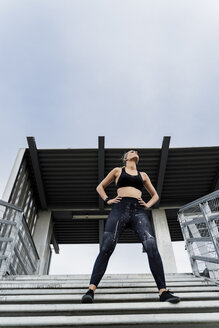 Sporty woman standing on stairs, with hands on hips - ERRF01484