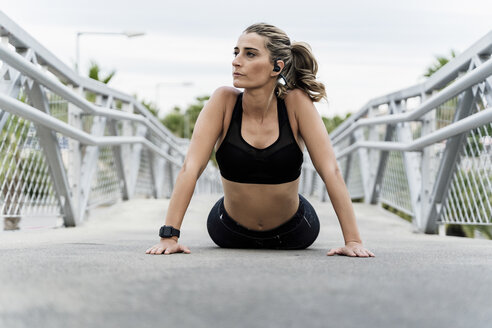 Sporty woman with headphones, working out on a bridge - ERRF01487