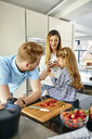 Happy family eating fresh strawberries in modern kitchen - ZEDF02327