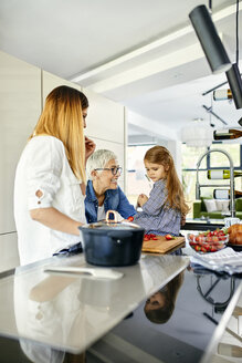 Mother, daughter and grandmother having fun, chopping strawberries in the kitchen - ZEDF02333