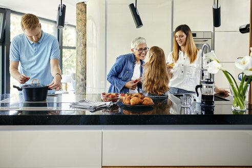 Three genaration family preparing food in kitchen - ZEDF02336