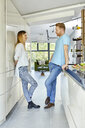 Young couple standing in kitchen, talking - ZEDF02345
