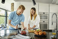 Couple standing in kitchen, preparing healthy breakfast, chopping fruits - ZEDF02348