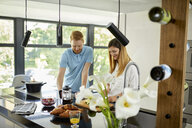 Couple standing in kitchen, preparing healthy breakfast, chopping fruits - ZEDF02351