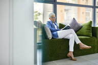 Senior woman sitting on couch, reading a book - ZEDF02366