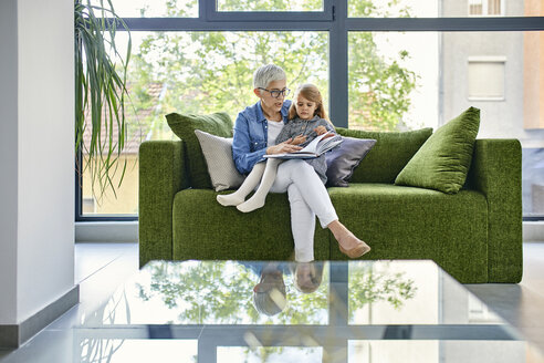 Grandmother sitting on couch with granddaughter, reading book together - ZEDF02369