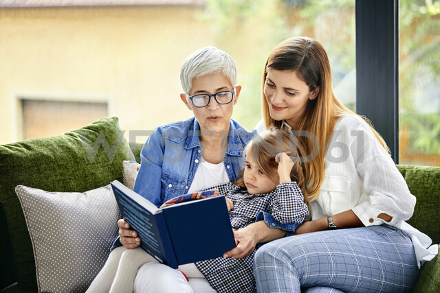 Mother, daughter and granddaughter sitting on couch, reading a book - ZEDF02372