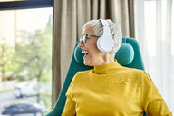 Senior woman sitting in armchair, listening music with headphones - ZEDF02411