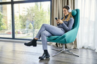 Woman sitting in armchair, listening music with headphones, using smartphone - ZEDF02414