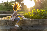 Young redheaded woman holding smartphone, headbangen in a park - AFVF03184