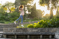Young redheaded woman jumping in a park - AFVF03187
