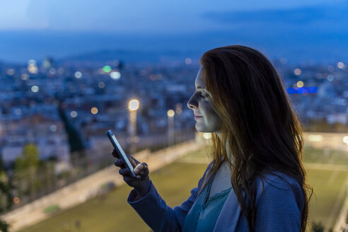 Young woman using smartphone on a view point at blue hour, Barcelona, Spain - AFVF03235