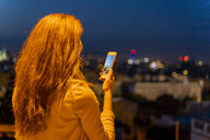 Young woman using smartphone on a view point at blue hour, Barcelona, Spain - AFVF03244