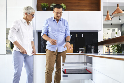 Man and mature woman talking in a kitchen retail store - ZEDF02430