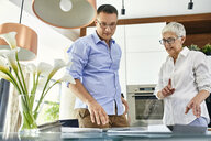Man and mature woman in a kitchen retail store examining material samples - ZEDF02433