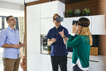 Couple wearing VR glasses shopping for a new kitchen in showroom - ZEDF02442