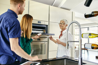 Shop assistant explaining oven to couple shopping for a new kitchen in showroom - ZEDF02448