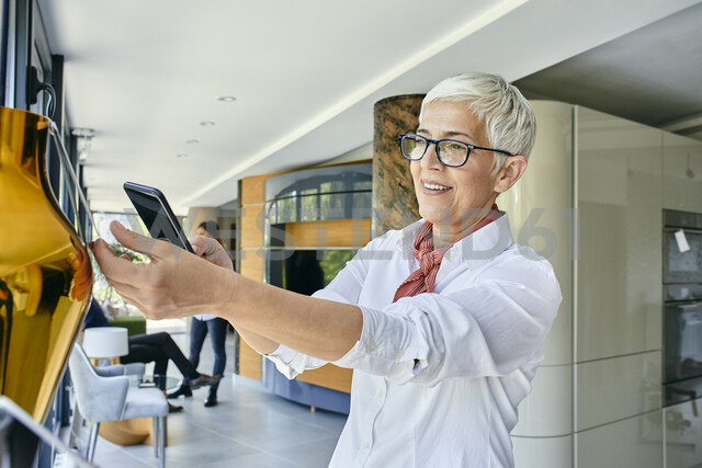 Mature woman scanning price tag with a smartphone in a showroom - ZEDF02475 - Zeljko Dangubic/Westend61