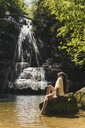 Young woman sitting on rock at a waterfall, Garrotxa, Spain - AFVF03260