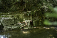 Young woman lying at a natural pool in forest, Garrotxa, Spain - AFVF03263