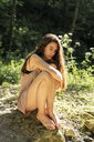 Young woman sitting on a rock in the forest, Garrotxa, Spain - AFVF03266