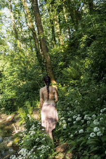 Rear view of barechested young woman walking in a lush forest, Garrotxa, Spain - AFVF03272
