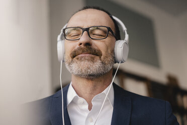 Mature businessman with closed eyes listening to music with headphones - KNSF05902