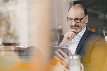 Mature businessman using tablet in a cafe - KNSF05914