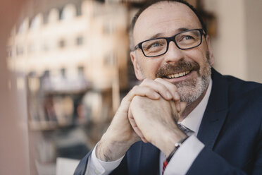 Portrait of smiling mature businessman in a cafe - KNSF05929