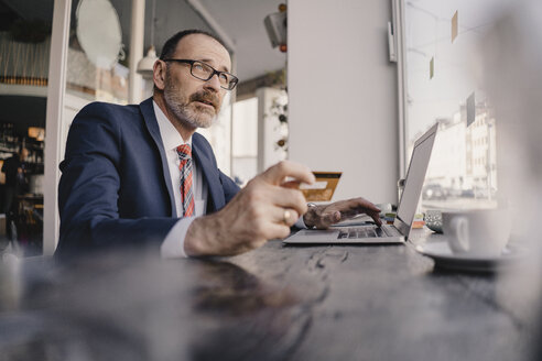 Mature businessman using laptop and credit card in a cafe - KNSF05932