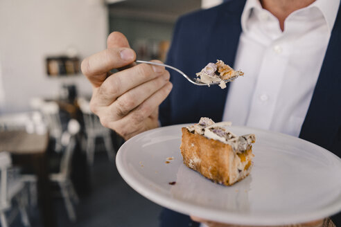 Close-up of businessman having a piece of cake in a cafe - KNSF05947