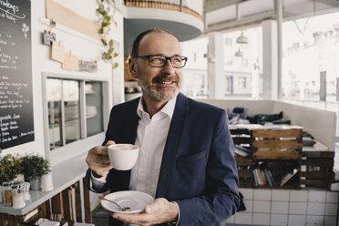 Mature businessman having a coffee in a cafe - KNSF05950
