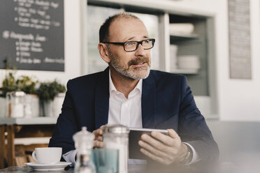 Mature businessman using tablet in a cafe - KNSF05953