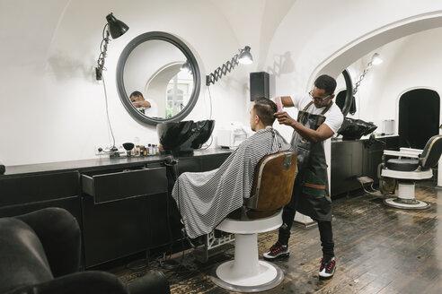 Barber cutting hair of a customer in barber shop - AHSF00493