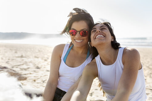 Portrait of two happy female friends on the beach - MGOF04069