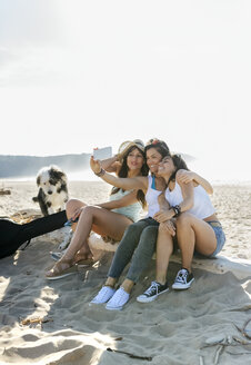 Happy female friends with dog taking a selfie on the beach - MGOF04072