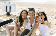 Happy female friends with beer bottles taking a selfie on the beach - MGOF04075