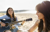 Two women with guitar on the beach - MGOF04087