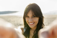 Portrait of a smiling young woman on the beach - MGOF04099