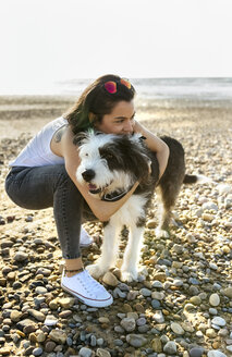 Young woman cuddling with dog on the beach - MGOF04105