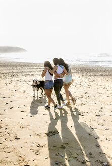 Three women with dog walking on the beach - MGOF04108
