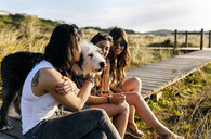 Three happy women with dog sitting on boardwalk in dunes - MGOF04114