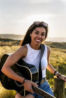 Portrait of a smiling young woman with guitar in dunes - MGOF04117