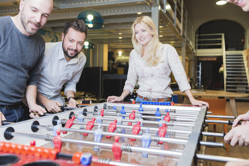 Happy colleagues playing foosball in office - FMOF00684