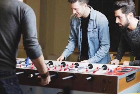 Colleagues playing foosball in office - FMOF00687