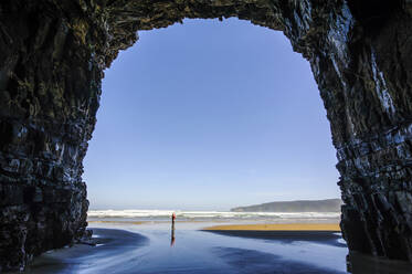 Woman standing in the giant Cathedral caves, The Catlins, South Island, New Zealand - RUNF02581