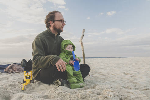 Father sitting with his baby daughter on a sandy beach, Curonian Spit, Lithuania - IHF00091