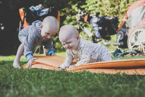 Baby girl and toddler boy with camping mat in grass - IHF00094