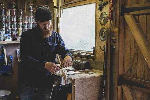Bearded man wearing black beanie standing at workbench in workshop, working on piece of wood. - MINF11284