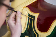 Close up of woman wearing glasses in a workshop, painting traditional wooden horse from merry-go-round. - MINF11578